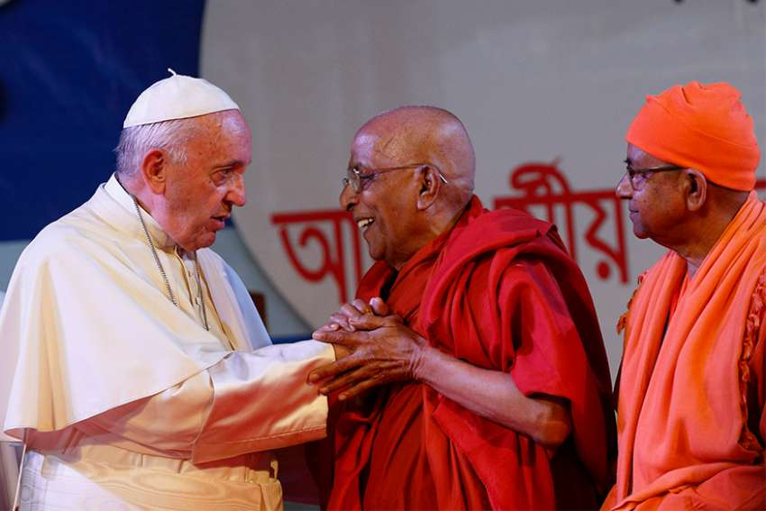 Pope Francis greets Buddhist representatives during an interreligious and ecumenical meeting for peace in the garden of the archbishop's residence in Dhaka, Bangladesh, Dec. 1, 2017.