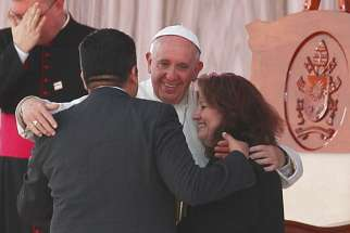 "Pope Francis embraces Humberto and Claudia Gomez, who are married civilly but not in the church, during a meeting with families at the Victor Manuel Reyna Stadium in Tuxtla Gutierrez, Mexico, Feb. 15. Pope Francis' postsynodal apostolic exhortation on the family, ""Amoris Laetitia"" (""The Joy of Love""), was to be released April 8. The exhortation is the concluding document of the 2014 and 2015 synods of bishops on the family."