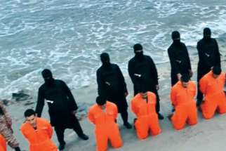 Men in jumpsuits purported to be Egyptian Christians held captive by the Islamic State militants kneel in front of armed men along a beach said to be near Tripoli, Libya, in this still image from an undated video. The video is said to show the beheading of 21 Egyptian Christians kidnapped in Libya.