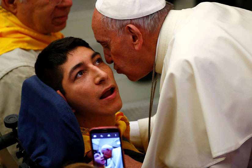 Pope Francis kisses a disabled young man during a special audience with members of Doctors with Africa at the Vatican May 7.