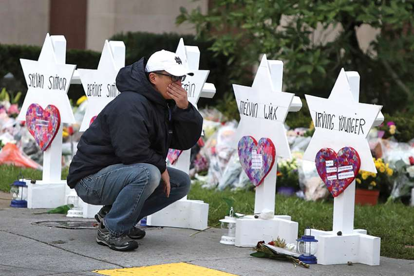 A young man reacts Oct. 29 at a makeshift memorial outside the Tree of Life synagogue in Pittsburgh.