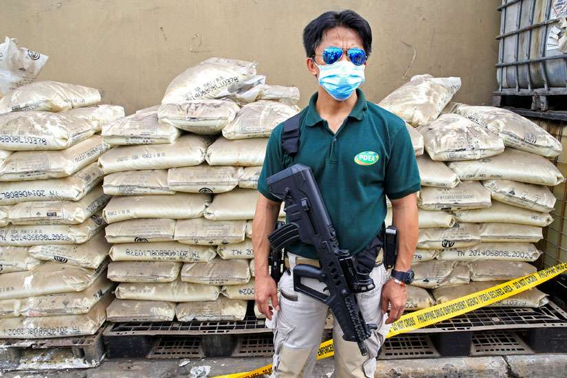 An agent of the Philippine Drug Enforcement Agency stands guard June 16 in front of chemicals used in the production of crystal meth, or Shabu, near Manila, Philippines. Philippine church leaders expressed words of caution in the wake of recent killings of suspected criminals, after voters there elected Rodrigo Duterte, who ran for president on the promise to rid the country of crime during his first six months in office.