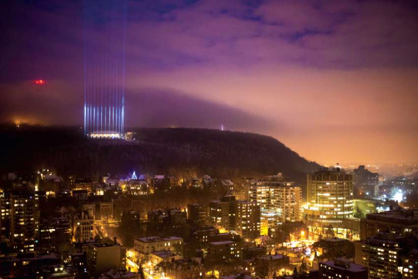 Fourteen light beams representing the 14 victims of the École Polytechnique massacre shine at Montreal's Mount Royal on the 25th anniversary of the slayings in 2014.
