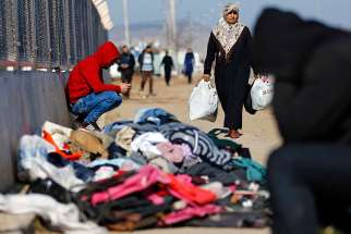 A refugee woman from Syria carries food while other displaced people sit near a border gate in Kilis, Turkey, Feb. 9. More than 30,000 people are stranded in northern Aleppo province after Turkish government forces closed border crossings.