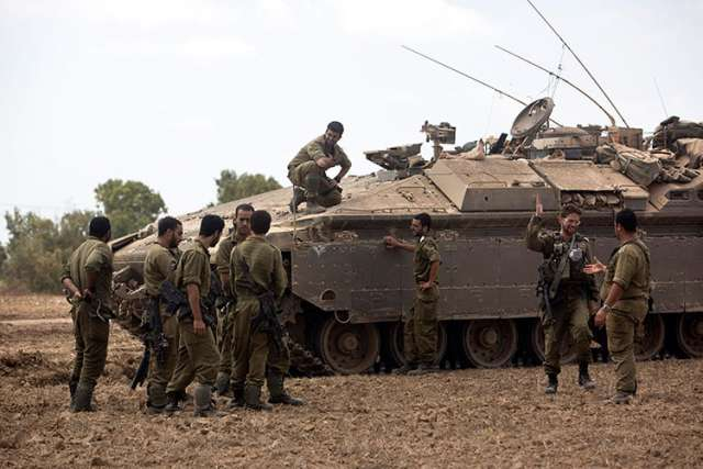 Israeli soldiers meet July 25 after ending their duty inside the Gaza Strip, on the Israeli side of the border.