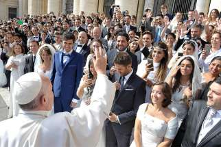 Pope Francis greets newly married couples during his general audience in St. Peter's Square at the Vatican Sept. 2015.