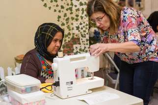 A volunteer works with a refugee from Afghanistan to help her learn how to use a sewing machine during an April 27 training session at a Catholic Charities program in Fredericksburg, Va.