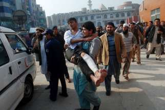 A man carries a student released from a hospital in Peshawar, Pakistan, after the Dec. 16 Taliban attack on the Army Public School.