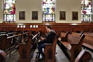 A woman reads a prayer book in the sanctuary of St. Mary Church in Appleton, Wis.