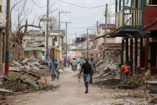 People walk past damaged buildings Oct. 9 after Hurricane Matthew swept through Port-a-Piment, Haiti.