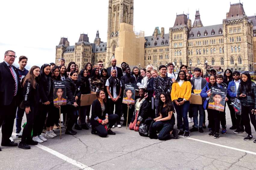 Immigration Minister Ahmed Hussen, centre, joins students and teachers who went to Ottawa to present postcards asking the government to address the causes of the global migration crisis.