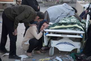 A woman mourns next to a dead body following an earthquake in Sarpol-e Zahab, Iran, Nov. 13. The Nov. 12 earthquake killed more than 400 people and injured more than 6,000 in Iran and Iraq.