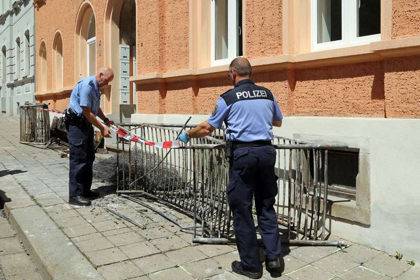 "Two police officers set up a barrier in front of a building June 28 after a fire destroyed a reception center for asylum seekers in Meissen, Germany. Cardinal Reinhard Marx of Munich-Freising, president of German bishops' conference, said an attack July 16 in the Bavarian town of Reichertshofen revealed that ""some groups"" were trying to ""sow hatred"" against migrants."