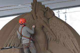 A worker sculpts an angel on a Nativity scene made entirely of sand in St. Peter's Square at the Vatican Nov. 26. The 52-foot wide sculpture is made of sand from Jesolo, an Italian seaside town near Venice.