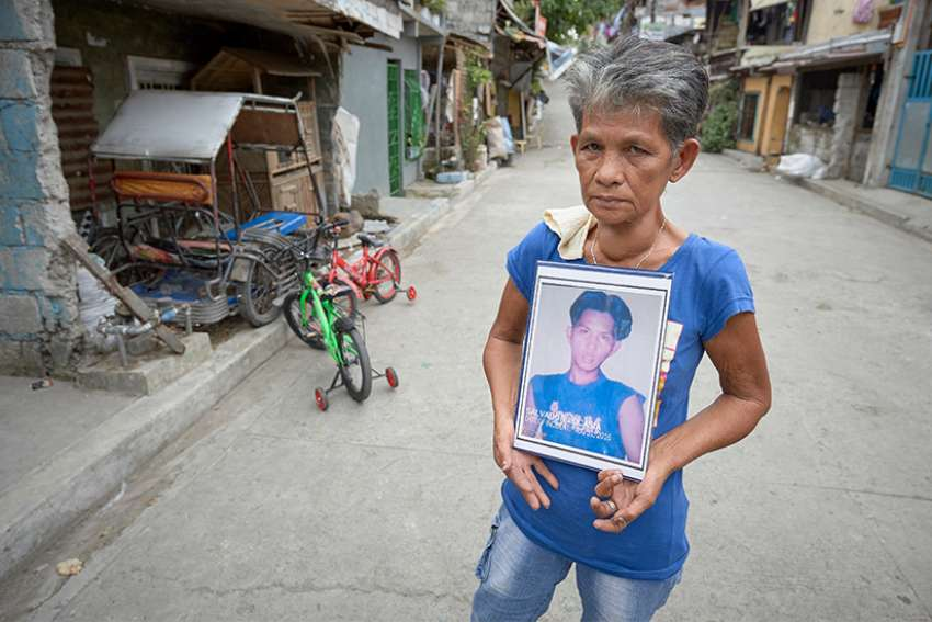 Irma J. Locasia holds a photo of her son Salvador J. Locasia Jr. in Manila, Philippines, Feb. 13, 2019. Her son was killed in a police operation on this street Aug. 31, 2016, a victim of the war on drugs of President Rodrigo Duterte.