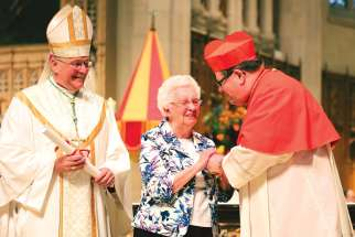 Sr. Teresita McInally receives the Pro-Ecclesia et Pontifice Cross from Quebec's Cardinal Gerald Lacroix as Hamilton Bishop Douglas Crosby looks on.