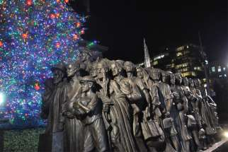 Timothy Schmalz's Angels Unawares is unveiled Dec. 8 in front of the  public Christmas tree put up by the Diocese of Brooklyn, N.Y., at Grand Army Plaza.