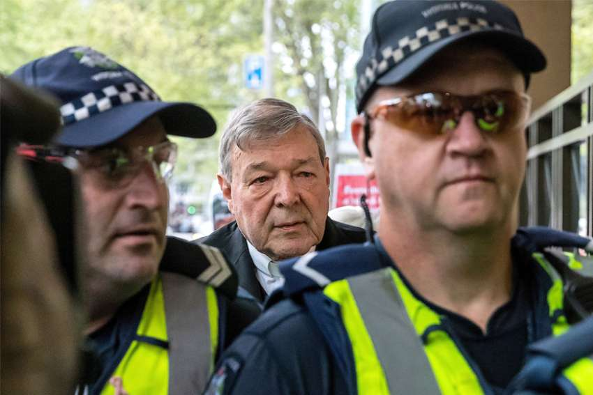 Australian Cardinal George Pell is seen in a 2017 file photo being escorted by police to the Melbourne Magistrates Court.