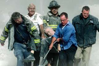 Rescue workers carry fatally injured New York City Fire Department chaplain, the Rev. Mychal Judge, from the wreckage of the World Trade Center in New York City on Sept. 11, 2001.