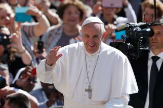Pope Francis greets the crowd during his general audience in St. Peter's Square at the Vatican May 18.