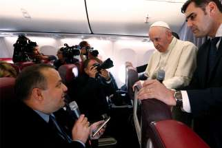 Pope Francis listens to a question from Romanian journalist Cristian Micaci aboard his flight from Sibiu, Romania, to Rome June 2.