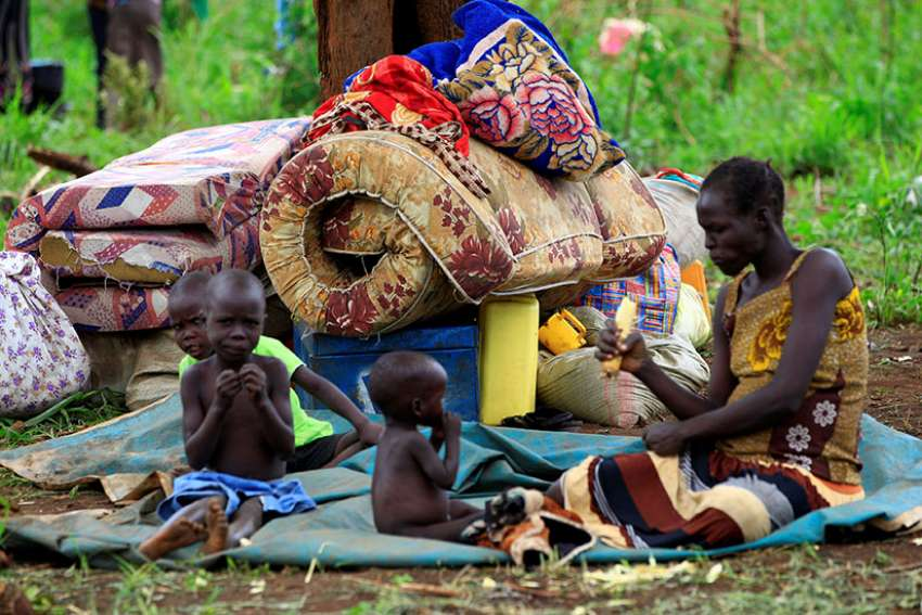 A family from South Sudan eats at a camp for displaced people in Lamwo, Uganda. As civilians are increasingly targeted in South Sudan's civil war, a bishop urged prominent community leaders speak out. (