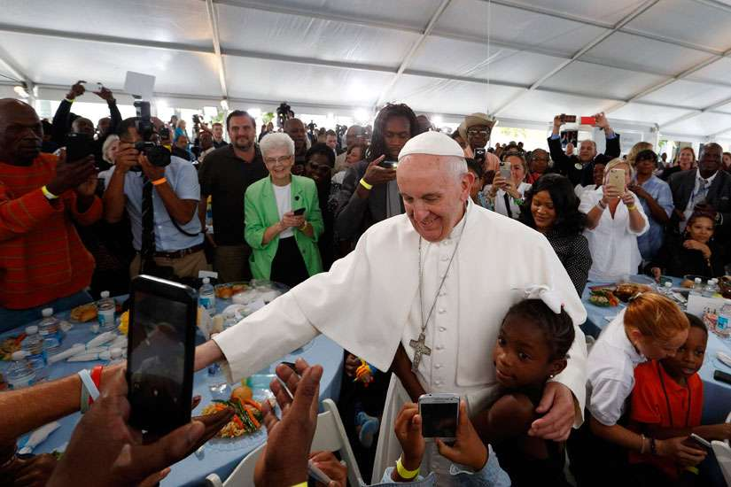 A girl hugs Pope Francis as he visits with people at St. Maria's Meals Program of Catholic Charities in Washington Sept. 24