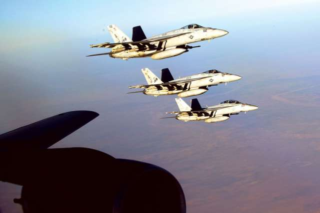 U.S. Navy F-18E Super Hornets make a formation after receiving fuel from a KC-135 Stratotanker over northern Iraq. These aircraft were part of a large coalition force striking Islamic State targets in Syria.
