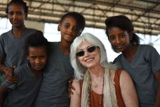 Emmylou Harris poses with young refugees at Adi-Harush refugee camp in northern Ethiopia. Harris, who has won more than a dozen Grammy awards during a 45-year career singing country music, is headlining a series of concerts this fall to benefit Jesuit Refugee Service.