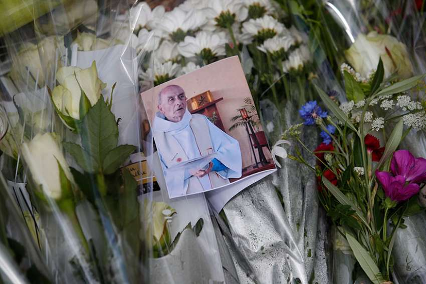 A photo of slain Father Jacques Hamel is seen among flowers at a makeshift memorial in Saint-Etienne-du-Rouvray, near Rouen, France, July 27, 2016.