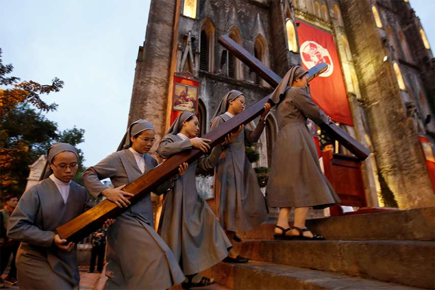Nuns carry a large wooden cross into St. Joseph's Cathedral April 14 in Hanoi, Vietnam, to celebrate Good Friday services.