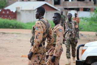 South Sudanese policemen and soldiers stand guard along a street following renewed fighting July 10 in Juba. Pope Francis have send a high-ranking cardinal to the war-torn country to urge peace.