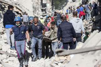 Rescuers carry an injured man in Amatrice, Italy, following an earthquake Aug. 24.