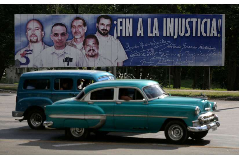 Cars in Havana drive past a banner Dec. 17 featuring five Cuban prisoners held in U.S. custody; two were previously released. U.S. President Barack Obama announced a shift in policy toward Cuba Dec. 17.