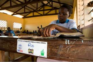 "A student at the Yedhi Primary School in the village of Boraimani, Kenya, does her school work on a desk provided by Catholic Relief Services. On March 3, the Population Research Institute and the Lepanto Institute said that CRS implemented the ""Healthy Choices 2"" program including the distribution of condoms and contraceptives under the federal President's Emergency Plan for AIDS Relief program. CRS called assertions that it had supplied birth control in the country as ""misleading, exaggerated and untrue."""