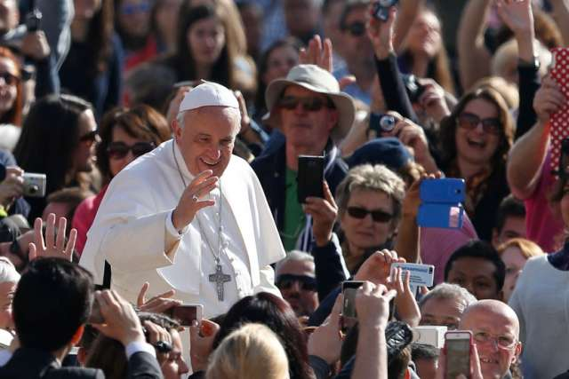 Pope Francis greets the crowd as he arrives for his general audience in St. Peter's Square at the Vatican April 1.