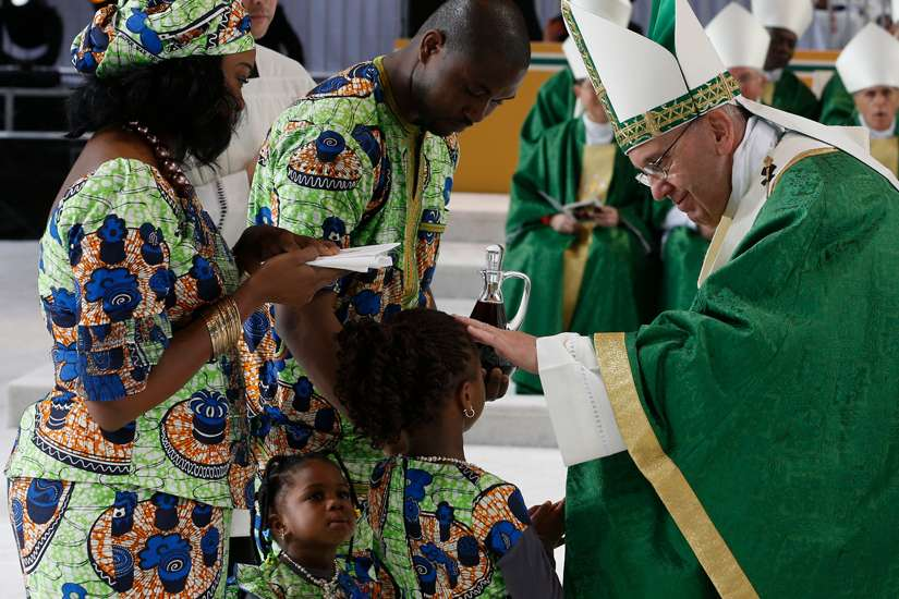 Pope Francis blesses a girl as her family presents offertory gifts during the closing Mass of the World Meeting of Families along Benjamin Franklin Parkway in Philadelphia Sept. 27, 2015. Pope Francis has asked families set aside time to pray both individually and together as a family.