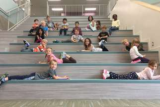 Grade one students relaxing on Ecole St. Elizabeth's presentation stairs.  Some 11,000 children moved into new P3 schools this fall in Saskatchewan.