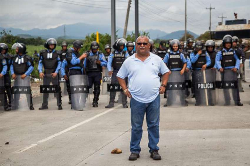 "Fr. Ismael ""Melo"" Moreno, S.J., a prominent human rights advocate in Honduras stands at a protest."