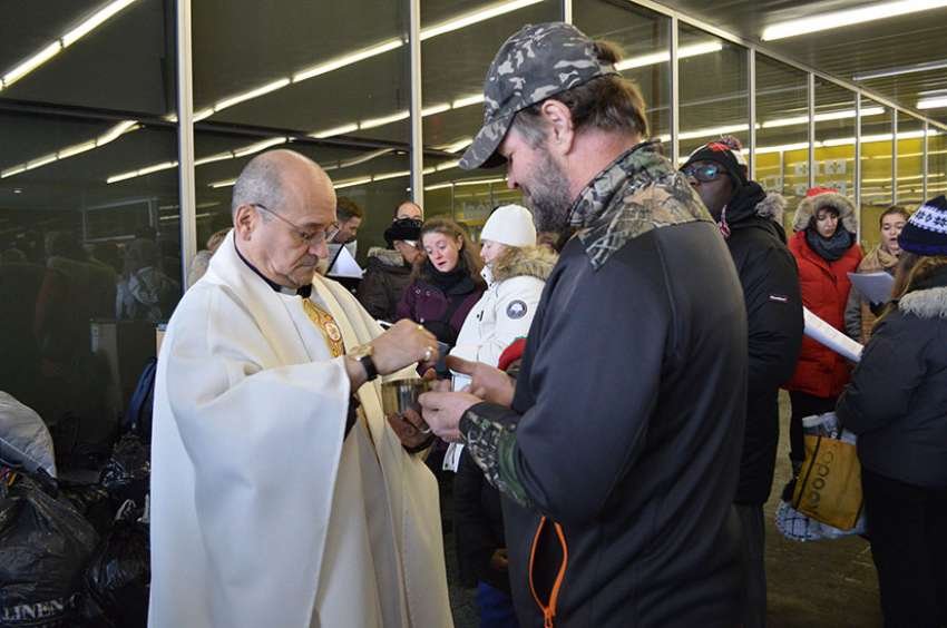 Father Claude Paradis of Montreal distributes Communion during an outdoor Christmas Eve Mass for the homeless people in downtown Montreal.