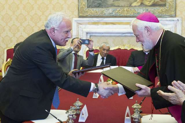 "Archbishop Paul Richard Gallagher, right, secretary for relations with states within the Holy See's Secretariat of State, and Palestinian Foreign Minister Riyad al-Malki, shake hands during a meeting at the Vatican June 26. The Vatican signed its first treaty with the ""State of Palestine"" on Friday, calling for ""courageous decisions"" to end the Israeli-Palestinian conflict with a two-state solution."