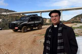 Bishop Oscar Cantu of Las Cruces, N.M., stands in front of an Israeli border police jeep Jan. 10 near the Palestinian land in the Cremisan Valley in Beit Jalla, West Bank.