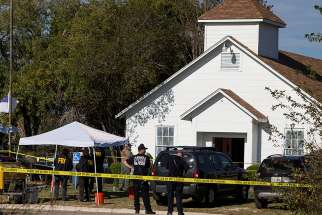 Law enforcement officers stand near the scene of a mass shooting Nov. 5 at the First Baptist Church in Sutherland Springs, Texas. A lone gunman entered the church during Sunday services taking the lives of at least 26 people and injuring several more.
