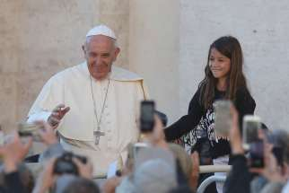 A girl prepares to meet Pope Francis during his general audience in St. Peter's Square at the Vatican Oct. 5.