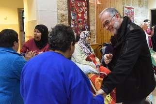 Bishop Lionel Gendron of Saint-Jean-Longueuil, Quebec, greets Palestinian women Jan. 17 in the Beit Emmaus Home for the elderly and disabled in Qubeibeh, West Bank.