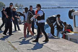 Coast Guard members help refugees to disembark April 17 at the port of Kalamata in Greece. The survivors told U.N. staff that they had been part of a group of between 100 and 200 people who departed from Libya the previous week. There are reports of up to 500 refugees drowning in the Mediterranean Sea.