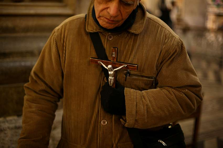 A man holds a crucifix at the cathedral in Santiago, Chile, May 18, 2018. Bishop Celestino Aos Braco of Copiapo, Chile, said April 4 in Rome that the Catholic Church in Chile must do everything possible to repair the damage caused by clergy sexual abuse and subsequent cover-up, and accept the decision of the courts investigating cases.