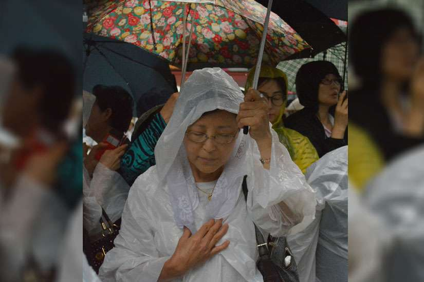 A woman prays with others in the rain outside Myongdong Cathedral in Seoul, South Korea, as Pope Francis celebrates a Mass for peace and for the reconciliation of North and South Korea inside Aug. 18. Many Catholic and non-Catholics braved the pouring ra in to try to get a glimpse of the pontiff at his last Mass before leaving South Korea.
