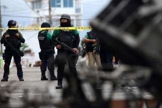 Police officers guard the municipal building in Catemaco, Mexico, Nov. 14 after it was set on fire following the disappearance of Father Jose Luis Sanchez Ruiz, pastor of Twelve Apostles parish . The outspoken priest, who had been reported missing in the state of Veracruz, was found alive, but with signs of torture.