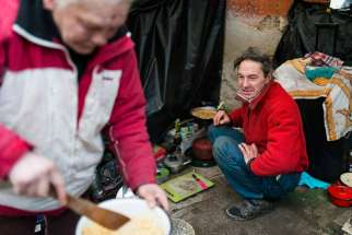 "A homeless couple cooks a meal outside their makeshift shelter in late January in Budapest, Hungary. Europe's top Catholic charitable agency has published a ""road map for social justice and equality,"" urging all church members to defend the poor and marginalized."